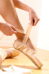 Ballet dancer tying slippers around her ankle woman ballerina pointe