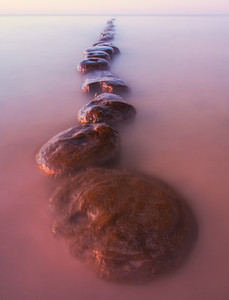 Baltic sea coast with old wooden pier photographed on long exposure
