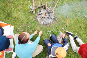 Barbecue in nature, group of people preparing sausages on fire