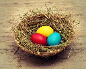 Basket with nest and colored eggs
