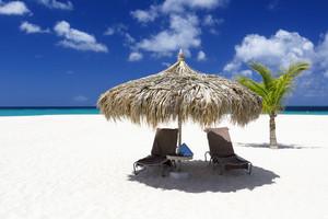 Beach chairs and umbrella on a white sand beach