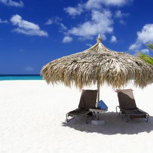 Beach chairs under an umbrella on a white sand beach