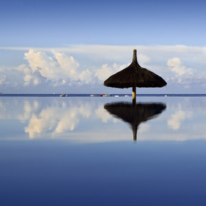 Beach umbrella reflected against a smooth swimming pool at a tropical resort