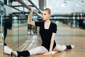 Beautiful ballerina doing stretching exercises in ballet class