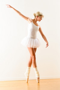 Beautiful ballerina on tiptoe with raised arm dancing pointe