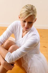 Beautiful ballerina rests sitting on studio floor woman ballet happy