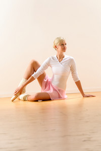 Beautiful ballerina sitting on floor holding ankle woman ballet exercise