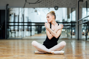 Beautiful ballerina sitting on the floor in ballet class
