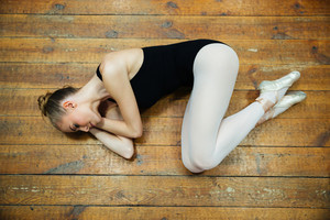 Beautiful ballerina sleeping on the wooden floor in ballet class
