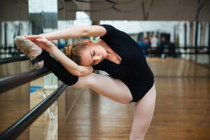Beautiful ballerina warming up in ballet class