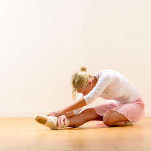 Beautiful ballerina warming up on the floor bending on knee