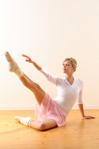 Beautiful ballet dancer lifting arm towards leg exercise woman ballerina