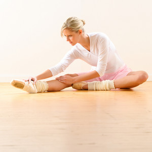 Beautiful ballet dancer stretching in the studio woman ballerina exercise