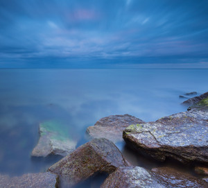 Beautiful Baltic sea landscape with stone breakwater. Tranquil long exposure landscape with moody blurred sky and water.