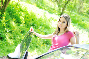 Beautiful blonde girl standing near by her car in a forest