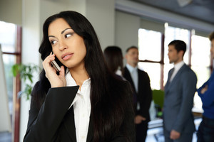 Beautiful businesswoman talking on the phone with colleagues on background