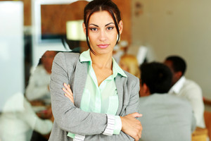 Beautiful businesswoman with arms folded standing in front of colleagues
