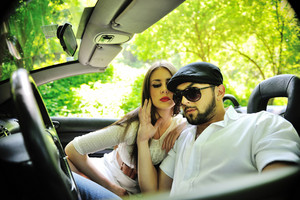 Beautiful couple in a sports car outdoors