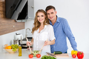 Beautiful couple standing and cooking together on the kitchen at home