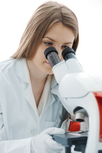 Beautiful female researcher using a microscope in a lab