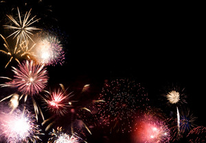 Beautiful fireworks going off with plenty of room for your text in the dark night sky.