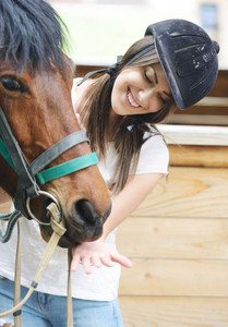 Beautiful girl riding taking a care of a horse on farm