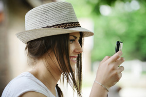Beautiful girl with hat typing on her mobile phone