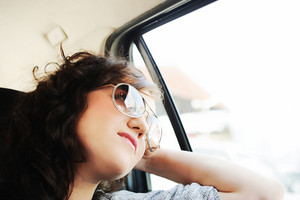 Beautiful happy girl in car, looking trough the window