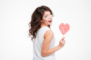 Beautiful happy woman holding lollipop and looking back at camera isolated on a white background