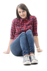 Beautiful joyful girl in checkered shirt sitting isolated on white