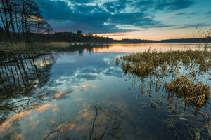 Beautiful lake after sunset with sky reflected in water. Polish lake landscape photographed in Mazury lake district. Place where swans sleeping.
