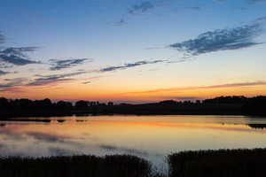 Beautiful lake landscape after sunset with sky reflected in water. Calm landscape