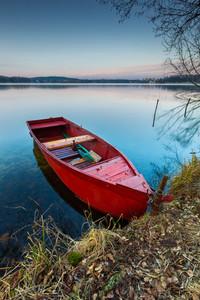 Beautiful lake landscape with boat on shore. Polish lake in Mazury lake district.