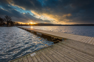 Beautiful lake landscape with jetty. Polish lake shore at cloudy weather sunset. Dramatic sky scene at sunset.