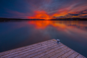 Beautiful lake landscape with vibrant sunset and pier. Long exposure landscape.
