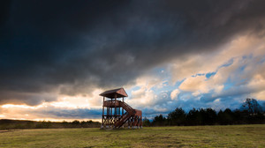 Beautiful landscape of watching tower under dramatic sky. Landscape with bad weather and vibrant colors.