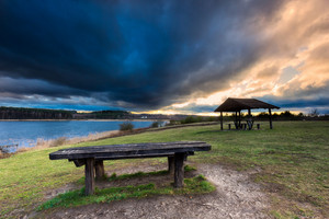 Beautiful landscape of wooden hut under dramatic sky. Landscape with bad weather and vibrant colors.