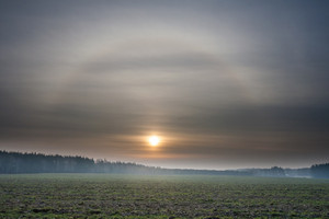 Beautiful landscape over green meadow with halo effect near sun