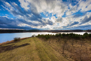 Beautiful landscape photographed from above (from tall observation tower). Early spring meadow on lake shore with forest under blue sky with clouds. Tranquil scene.