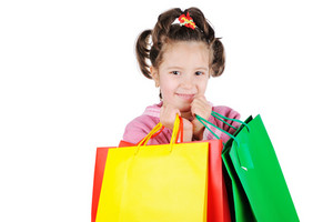Beautiful little girl holding shopping bags isolated