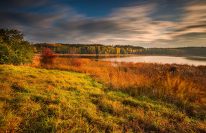 Beautiful long exposure autumnal landscape of lake and and colorful plants photographed at sunset. Amazing dreamy landscape.
