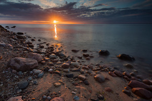 Beautiful long exposure landscape of rocky sea shore. Tranquil scene of Baltic sea at sunrise near Gdynia in Poland.
