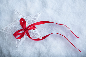 Beautiful magical vintage white star tied with a red ribbon on a white snow background. Winter and Christmas concept.