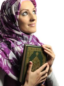 Beautiful Muslim girl holding Koran