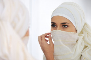 Beautiful Muslim woman looking at mirror and putting her scarf