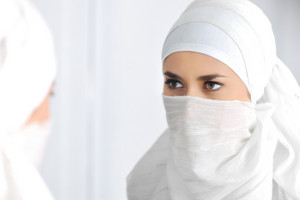 Beautiful Muslim woman looking at mirror