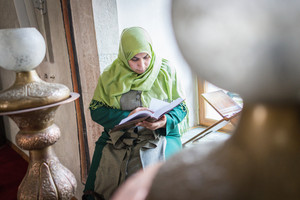 Beautiful Muslim young woman inside the mosque reading holy book Koran