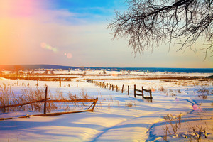 Beautiful rural landscape at sunset in snowy winter
