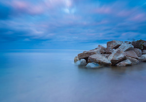 Beautiful seascape with stony breakwater photographed on long exposure.
