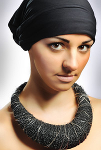 Beautiful sensual young woman with necklace and scarf on head